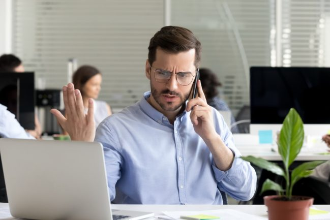 Picture of a man on the phone trying to settle a commercial real estate disagreement or dispute